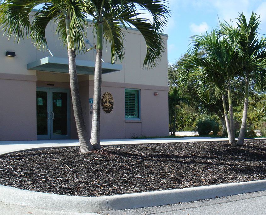 Stucco building with palm trees in front that is the Hospice and Palliative Care Wing